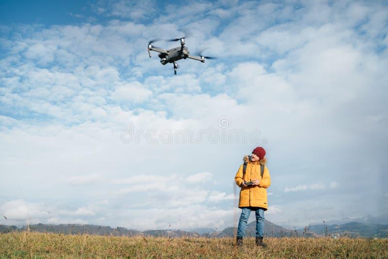 Tienerjongen verkleedde gele jas om een moderne digitale drone te besturen met behulp van een afstandsbediening stock foto