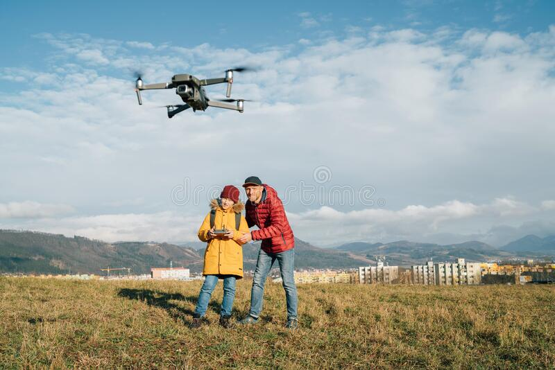 Tienerjongen zoon verkleedde gele jas en vader piloot een moderne digitale drone met behulp van een afstandsbediening Moderne tec royalty-vrije stock foto