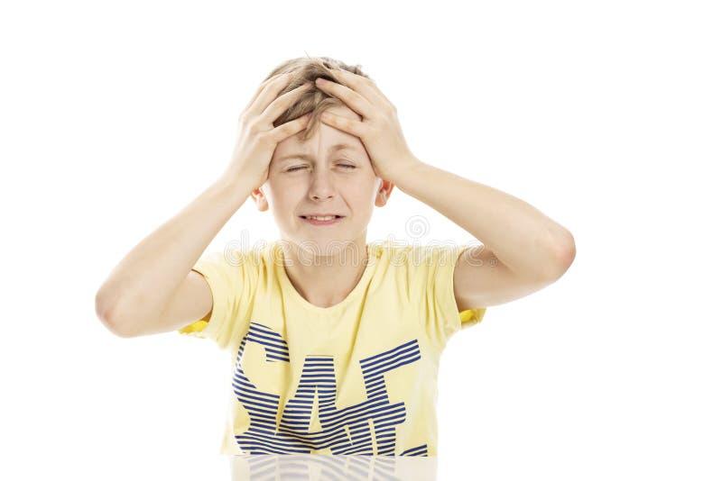Tienerkerel die boos terwijl het zitten bij de lijst gillen Over witte achtergrond stock fotografie