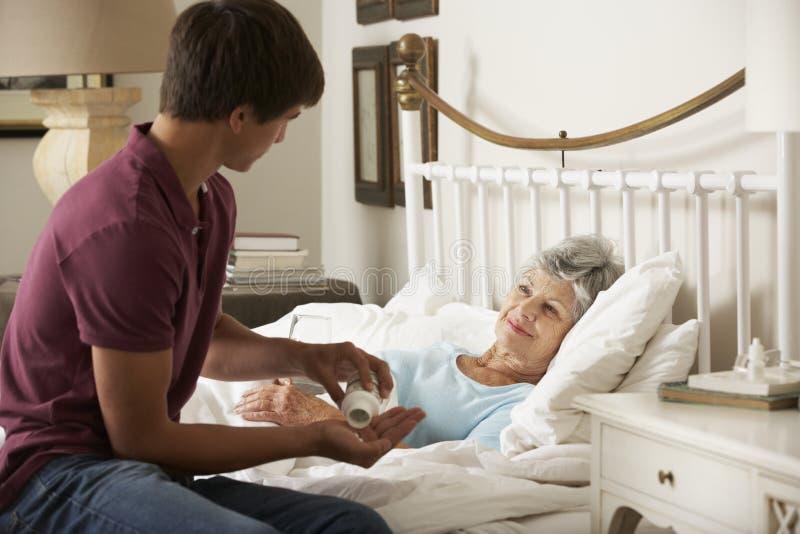 Tienerkleinzoon die Grootmoedermedicijn in Bed thuis geven royalty-vrije stock afbeelding