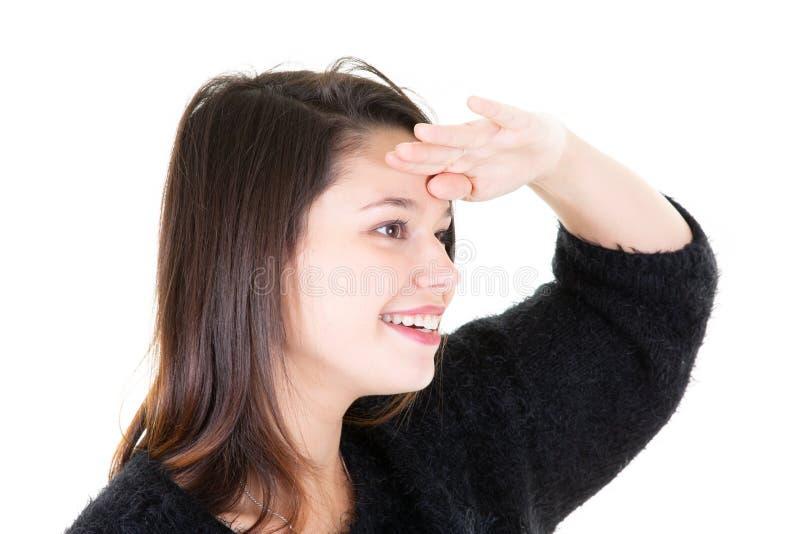 Tienermeisje dat op witte achtergrond ver weg met hand kijkt om te kijken iets stock foto's