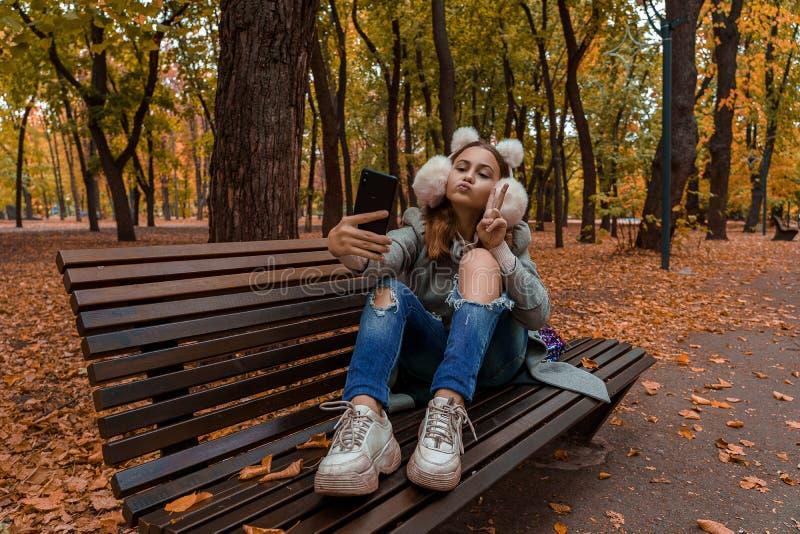 Tienermeisje in de bontkoptelefoon maakt zichzelf in het najaar stock foto