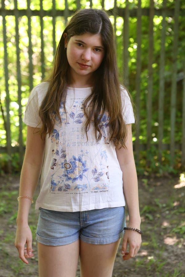 Tienermeisje in de roze kleding van de de zomermanier op de groene achtergrond van het tuinland royalty-vrije stock fotografie