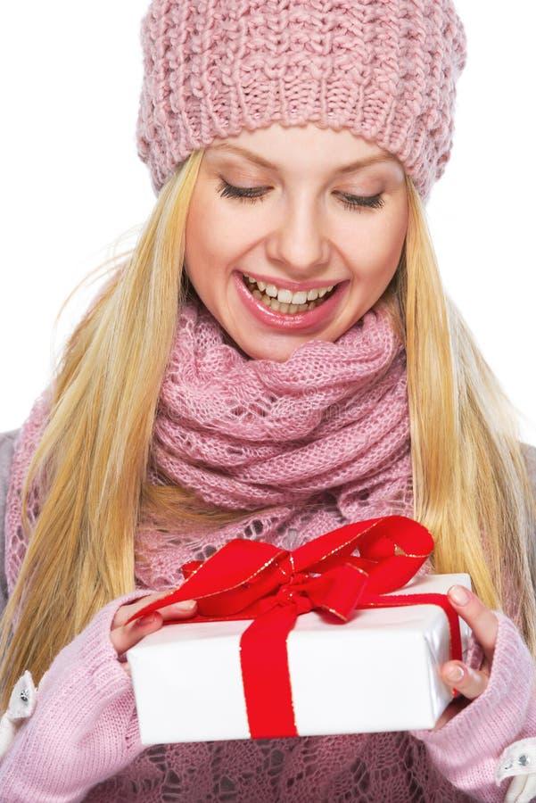 Tienermeisje in de winterhoed en sjaal met het voorstellen van doos royalty-vrije stock fotografie