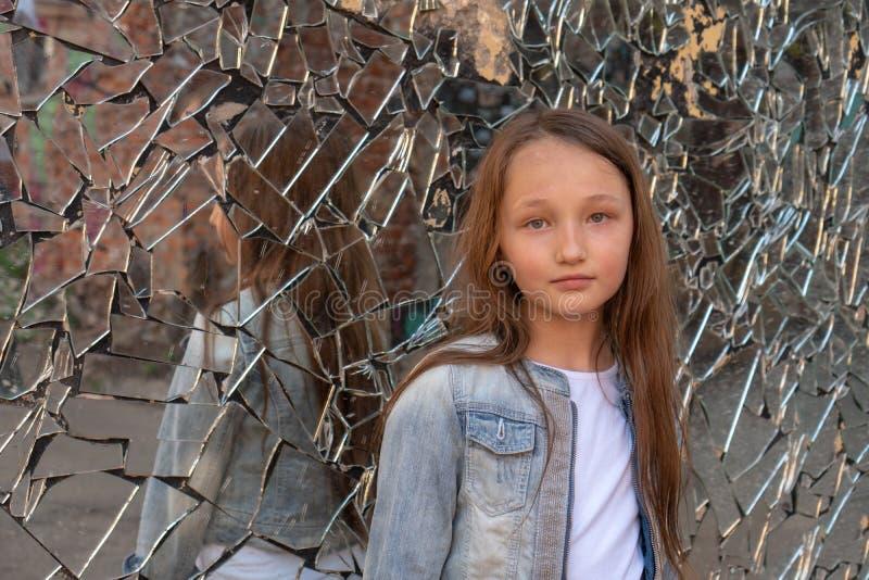 Tienermeisje die de camera bekijken Bezinning in een gebroken spiegel ongeveer de problemen van adolescenten Overgangsleeftijd royalty-vrije stock afbeelding