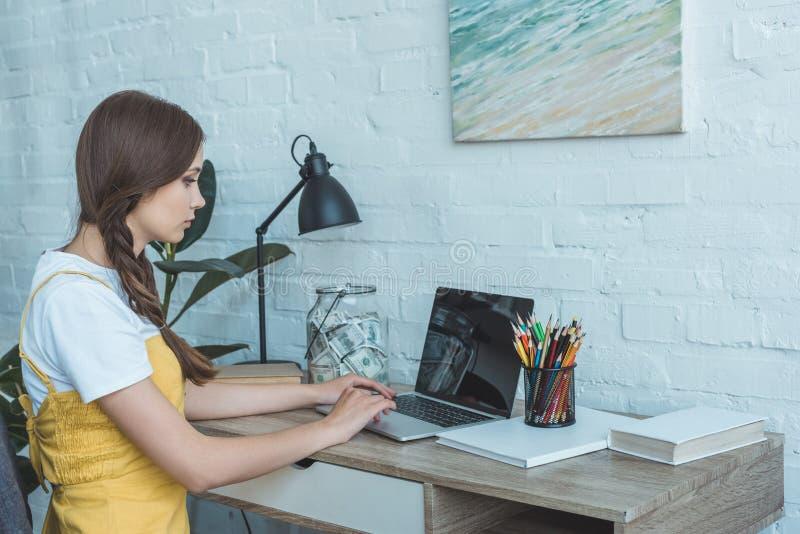 tienermeisje die laptop en lijst met besparingen gebruiken royalty-vrije stock afbeelding