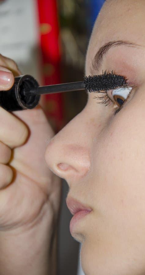Tienermeisje die mascara op haar wimpers toepassen stock fotografie