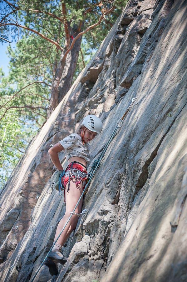Tienermeisje die op bergmuur beklimmen stock foto's