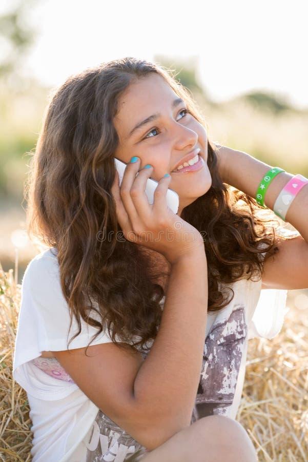 Tienermeisje die op telefoon in openlucht spreken stock afbeeldingen