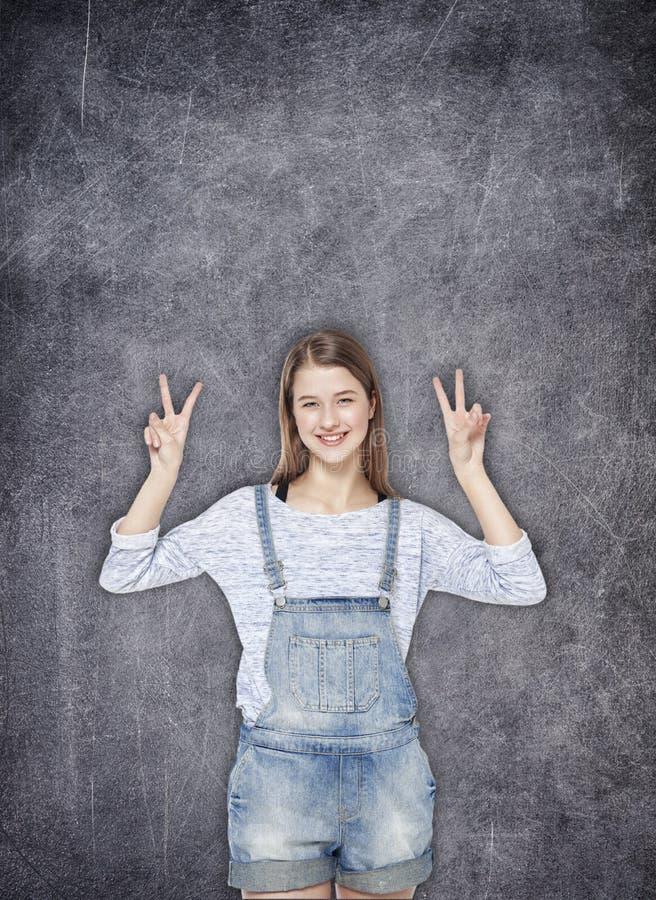 Tienermeisje die overwinningsteken op de bordachtergrond tonen stock afbeeldingen