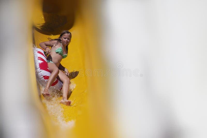 Tienermeisje die pret op een waterdia hebben in een waterpark stock afbeeldingen
