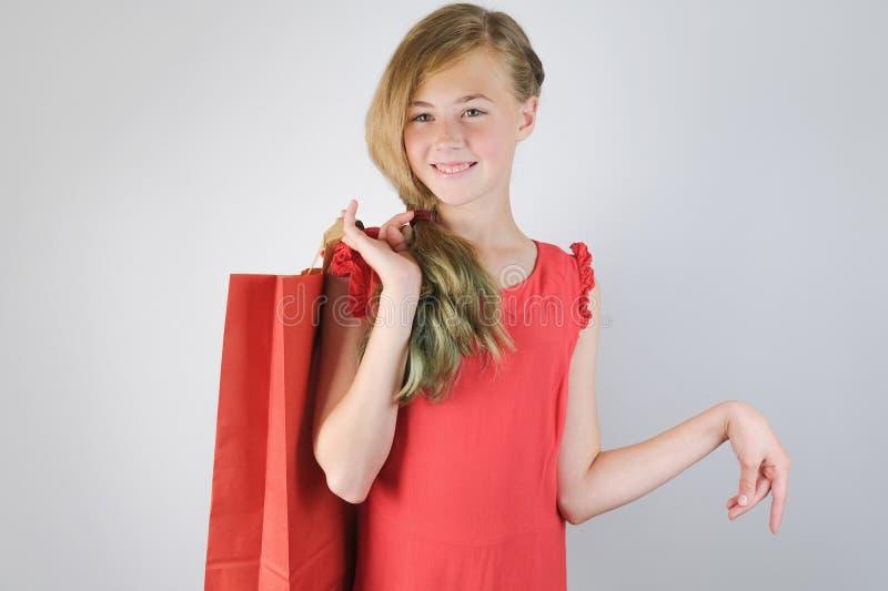 Tienermeisje die in rode kleding een het winkelen zak in haar hand houden, het glimlachen en status over grijze achtergrond stock foto