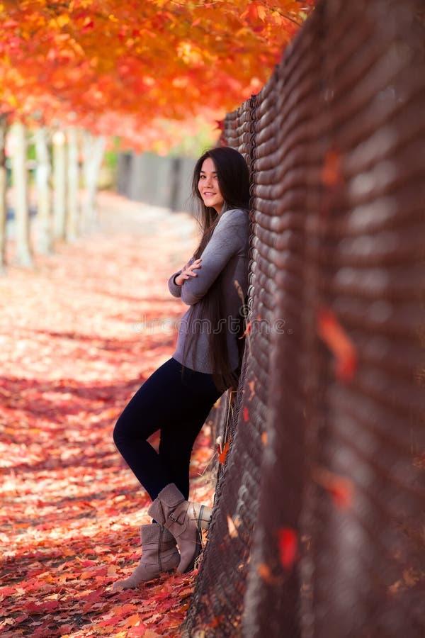Tienermeisje die tegen omheining onder luifel van esdoornbomen leunen royalty-vrije stock foto's