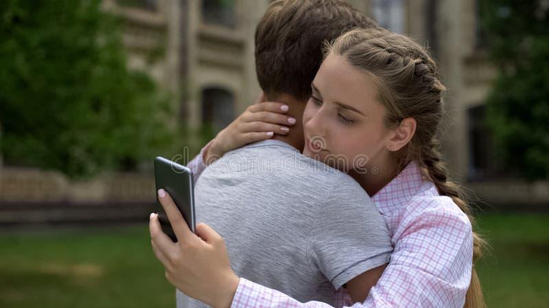 Tienermeisje die telefoon met behulp van, die vriend in plaats van echte mededeling, concept koesteren stock afbeeldingen