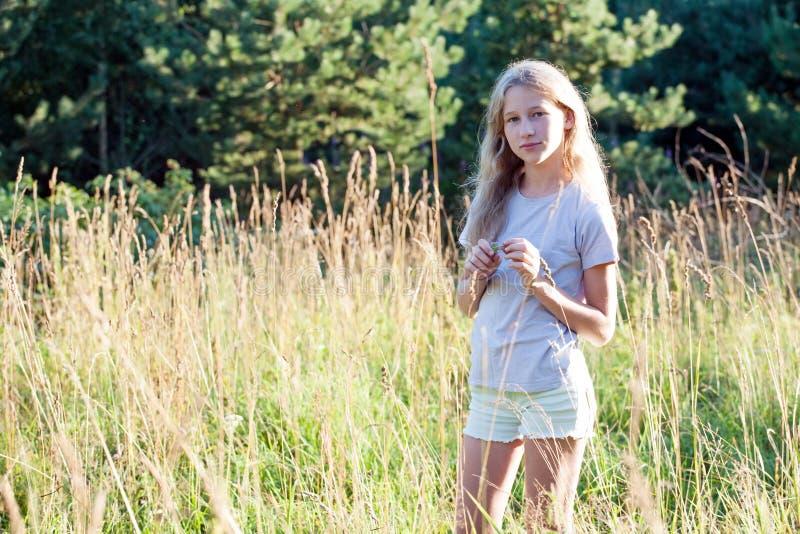 Tienermeisje die zich op de achtergrond van de de zomerweide bevinden royalty-vrije stock foto