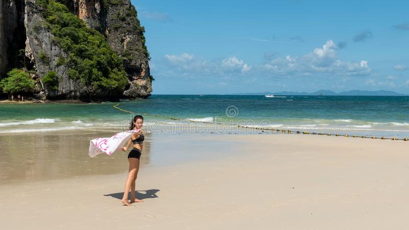Tienermeisje die zich op tropisch strand met handdoek bevinden royalty-vrije stock afbeeldingen