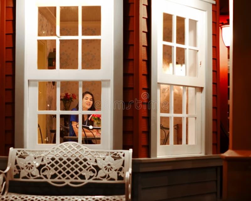 Tienermeisje door venster huis dat van buiten wordt gezien stock foto