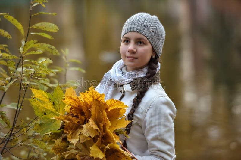 Tienermeisje in het de herfstpark met esdoornbladeren stock foto's