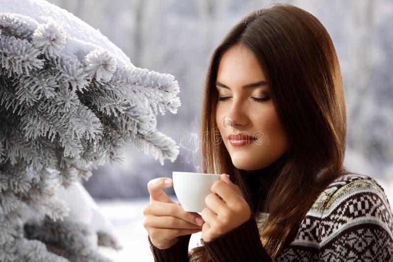 Tienermeisje het drinken koffie over de achtergrond van de de winteraard stock foto