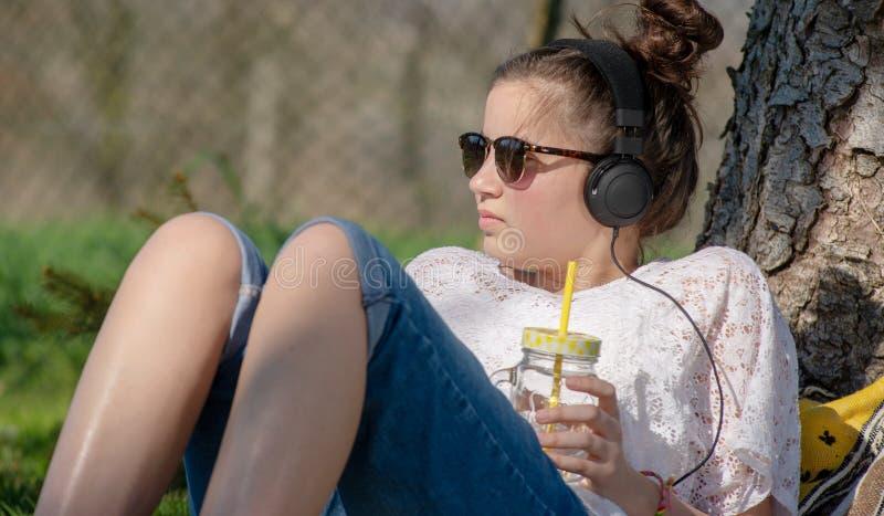 Tienermeisje het luisteren muziek en drinkwater in het park royalty-vrije stock afbeelding