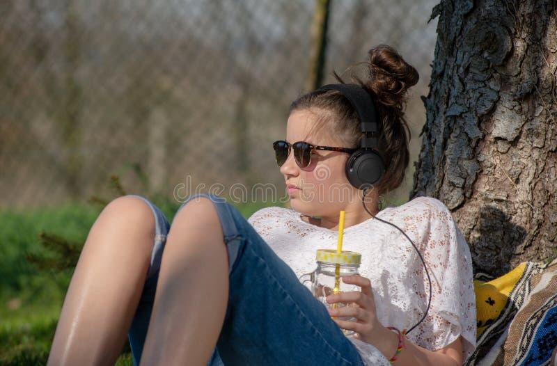 Tienermeisje het luisteren muziek en drinkwater in het park stock fotografie