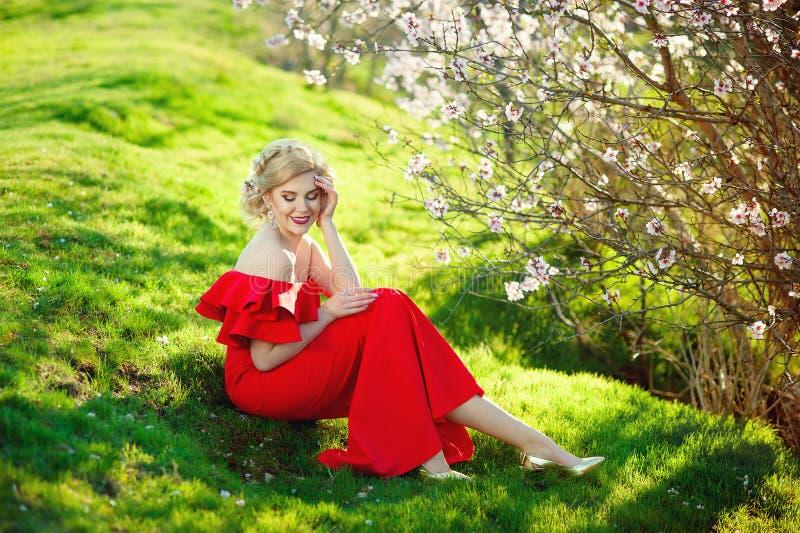 Tienermeisje het mooie vrolijke genieten van over bloeiende de boomachtergrond van de de lenteabrikoos stock foto