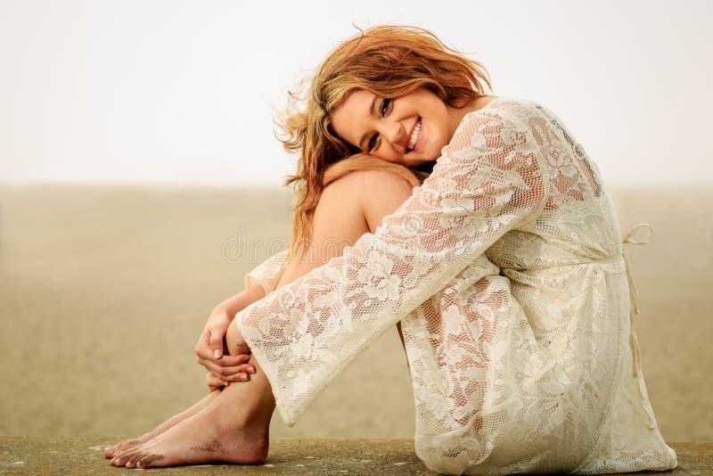 Tienermeisje het ontspannen op een muur met zandige voeten royalty-vrije stock afbeelding