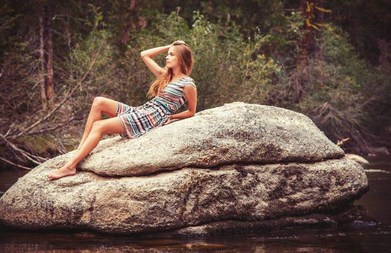 Tienermeisje het ontspannen op grote rots royalty-vrije stock afbeeldingen