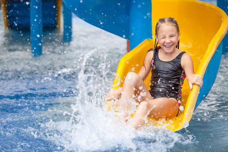 Tienermeisje het spelen in het zwembad op dia stock foto
