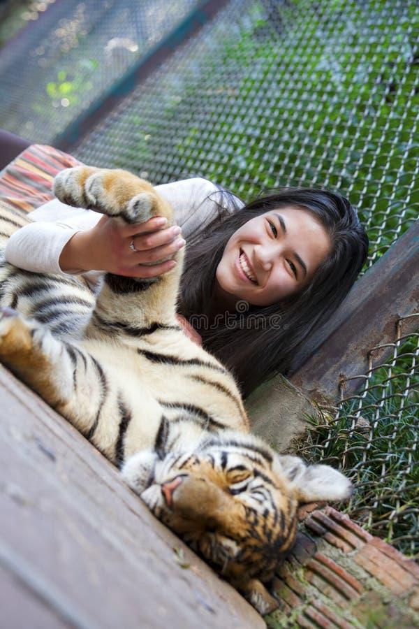 Tienermeisje het spelen met tijgerwelp binnen kooi stock afbeelding