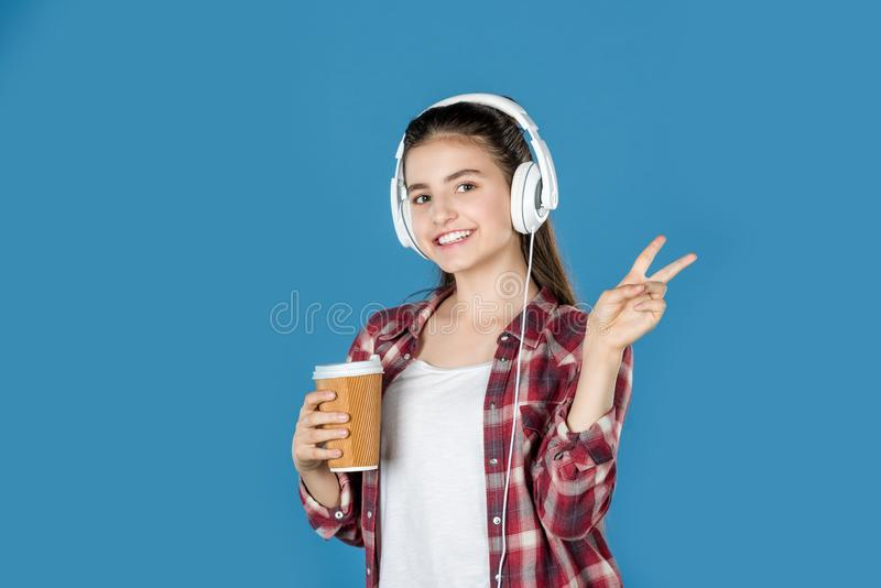 tienermeisje in hoofdtelefoons met koffie die vredesteken tonen stock foto