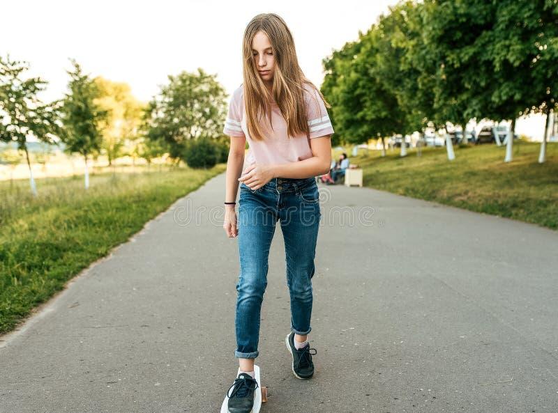 Tienermeisje 11-13 jaar oud, in de zomer in de stad, die een skateboard berijden Lang haar, rust in park na lessen stock foto's