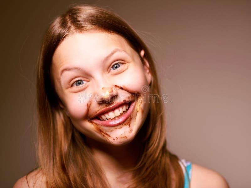 Tienermeisje met chocolade op haar gezicht stock afbeeldingen
