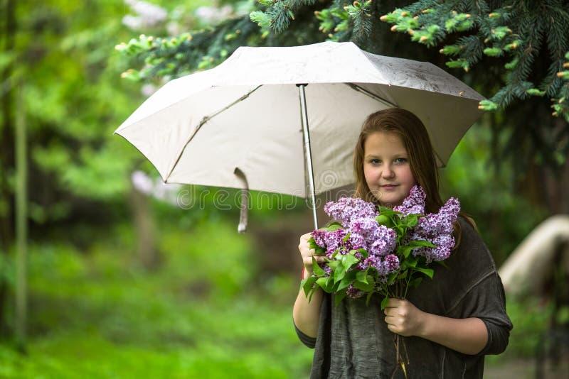 Tienermeisje met een boeket die van seringen, zich onder een paraplu bevinden stock foto