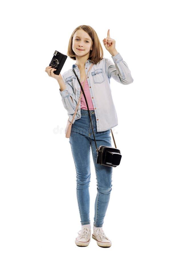 Tienermeisje met een camera, volledige lengte, die op witte achtergrond wordt geïsoleerd stock afbeelding