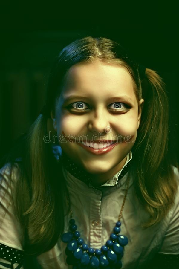 Tienermeisje met een sinistere glimlach stock fotografie