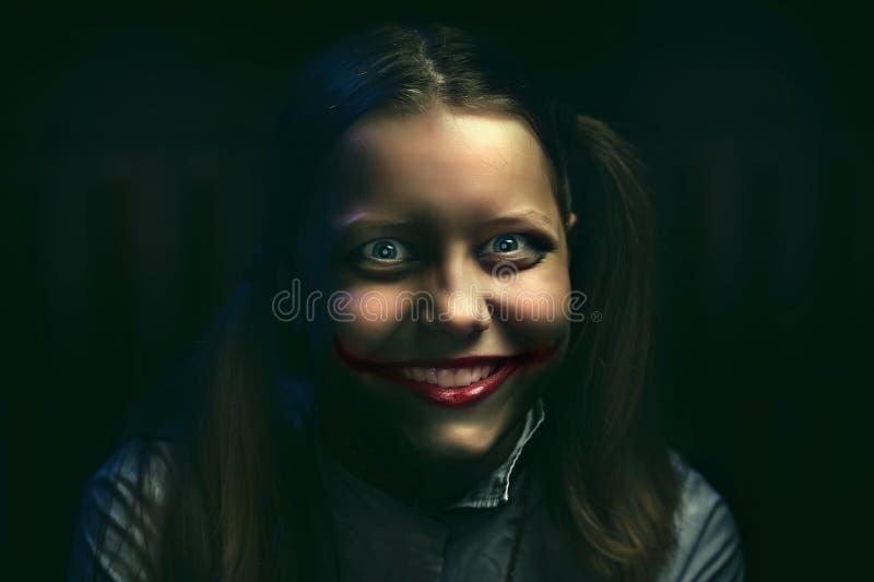 Tienermeisje met een sinistere glimlach stock foto