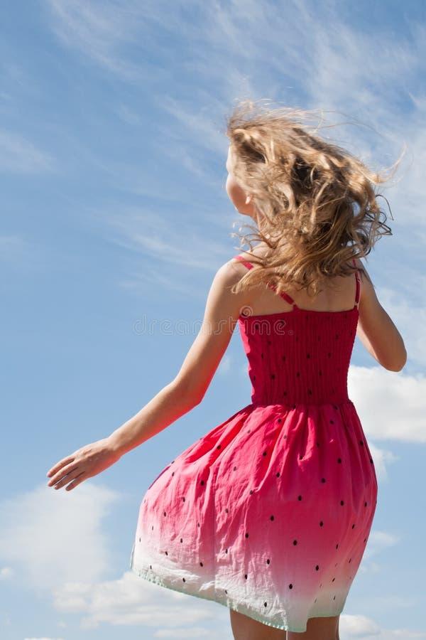 Tienermeisje met lang blond haar dat terugstaat in mooie zomerjurk stock afbeeldingen