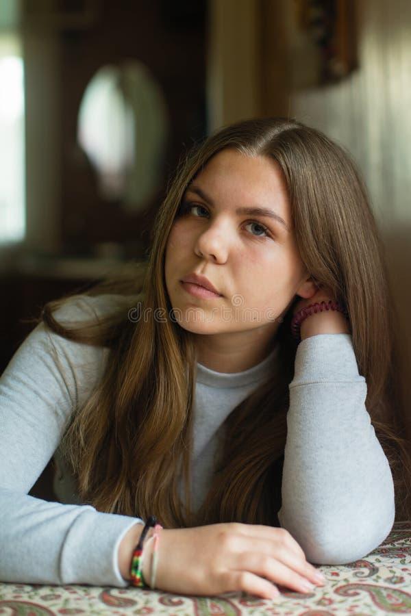 Tienermeisje met lange haarzitting bij de lijst in zijn huis royalty-vrije stock afbeeldingen