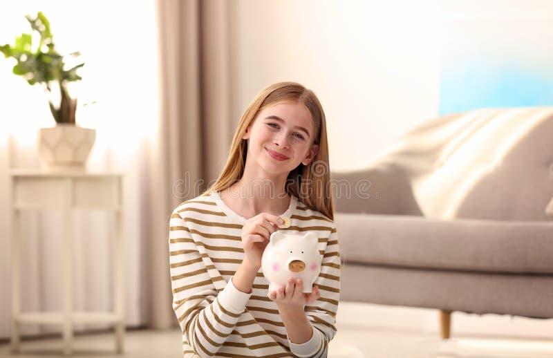 Tienermeisje met spaarvarken en geld stock afbeelding