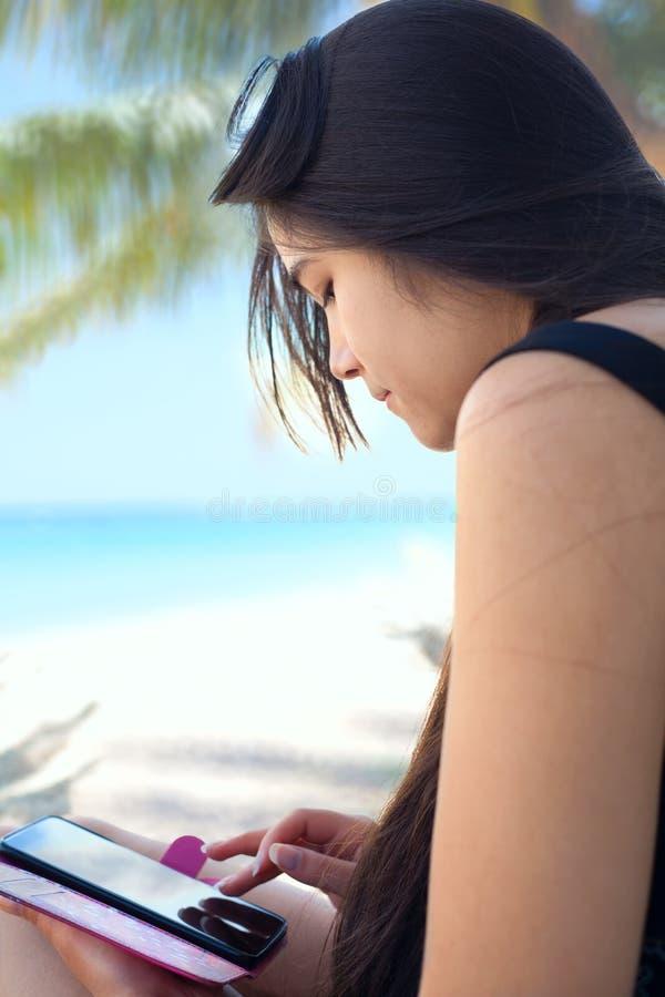 Tienermeisje op Hawaiiaans strand die cellphone gebruiken onder kokospalmen stock foto's
