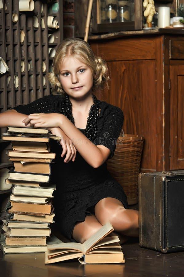 Tienermeisje in retro stijl met een stapel boeken stock fotografie