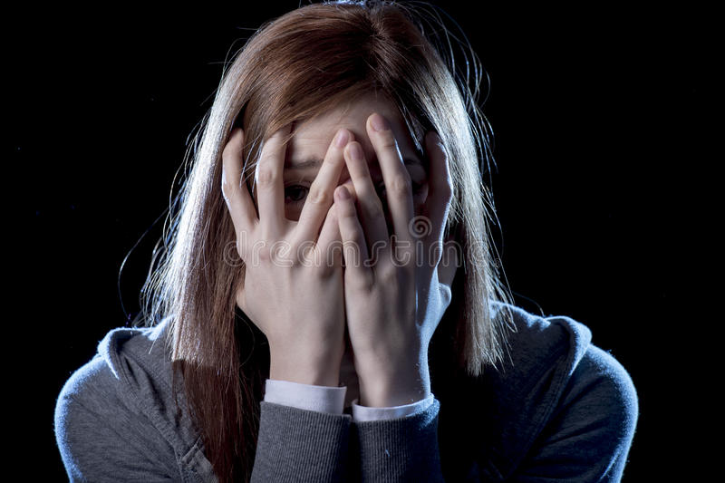 Tienermeisje in spanning en pijn die aan depressie lijden die droevig en in de uitdrukking van het vreesgezicht wordt doen schrik stock afbeelding