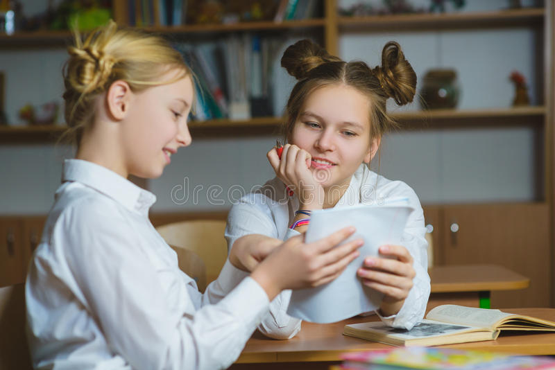 Tienermeisjes in de het schoolbibliotheek of klaslokaal, die wat bespreken zij leren stock foto