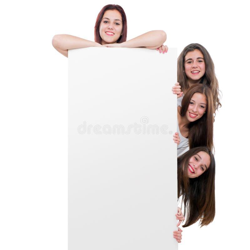 Tienermeisjes die blanc aanplakbord houden stock afbeeldingen