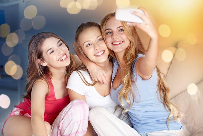 Tienermeisjes die met smartphone selfie thuis nemen stock foto's
