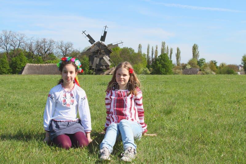 Tienermeisjes die in nationale kleren op het gras in het platteland zitten stock afbeelding