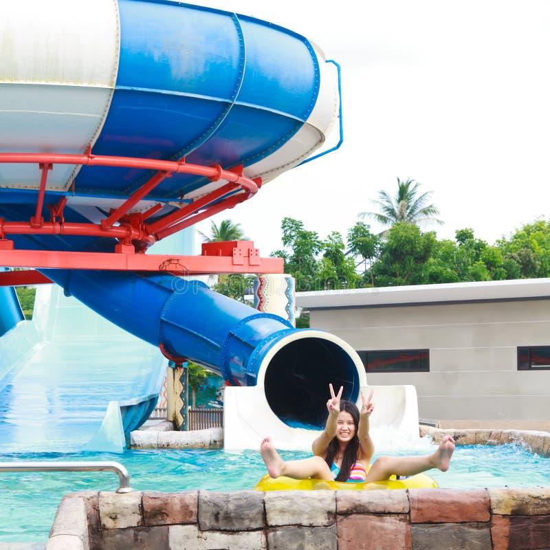 Tienermeisjes die pret met grote schuiven in aquapark hebben royalty-vrije stock afbeeldingen