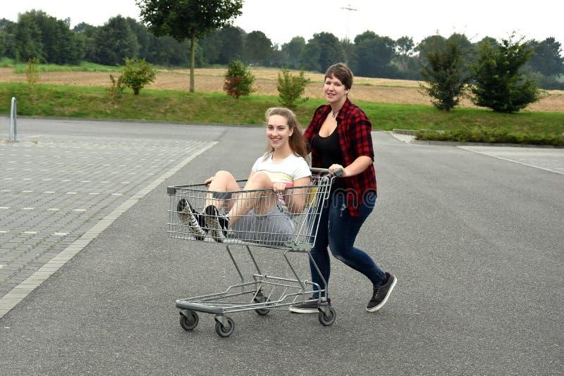 Tienermeisjes met boodschappenwagentje royalty-vrije stock afbeelding