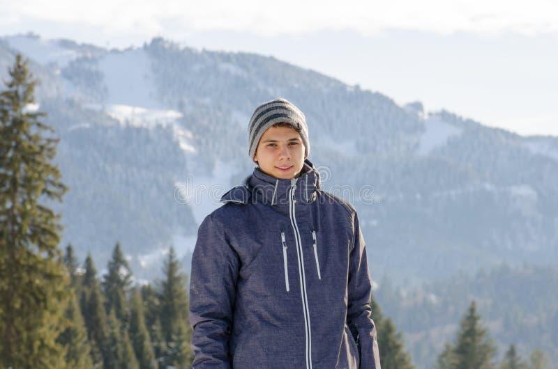 Tienermens die in de winterjasje bij bergen met skispoeling glimlachen stock fotografie
